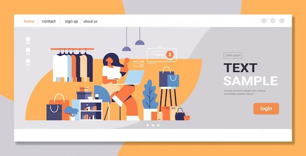 Donna con il computer portatile utilizzando il concetto di shopping online di applicazione del computer grande negozio di moda femminile vestiti boutique interno piatto spazio copia integrale