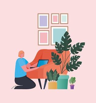 Donna con il computer portatile che lavora alla progettazione arancione della sedia del tema del lavoro da casa