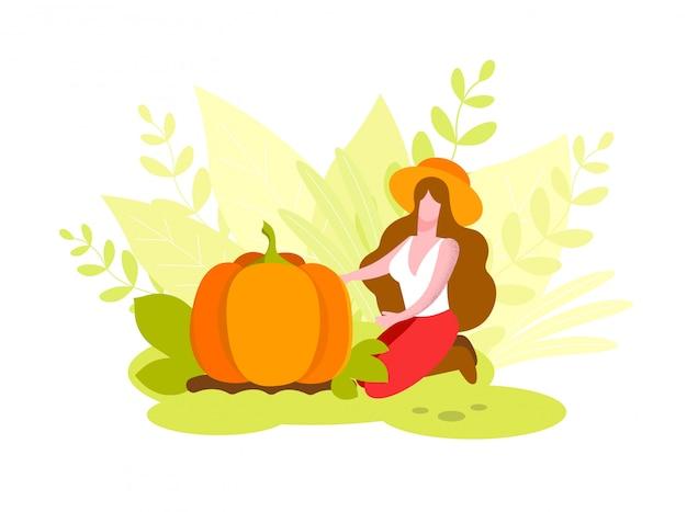 Donna con i capelli lunghi. in cappello si siede vicino a big pumpkin