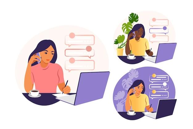 Una donna lavora su un computer portatile e parla al telefono seduto a un tavolo a casa con una tazza di caffè e documenti