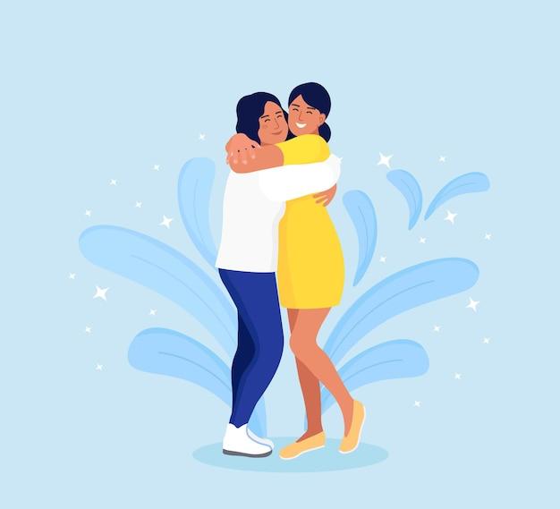 Donne che si abbracciano con un volto sorridente. felice incontro di due amici. concetto di amicizia, cura e amore