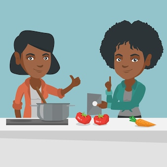 Donne in cerca di una ricetta su una tavoletta digitale.