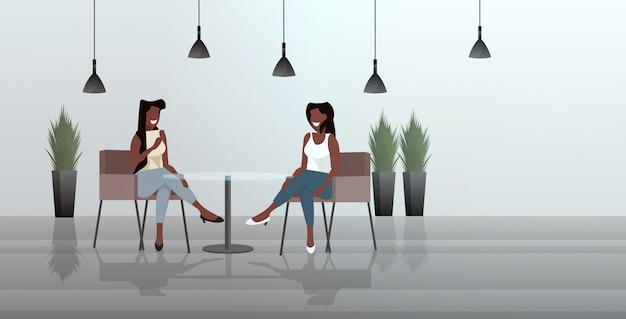 Donne sedute al tavolo del caffè durante la riunione moderna nel ristorante