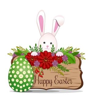 Tavola di legno con iscrizione di saluto di pasqua felice composizione di primavera con cartello in legno e coniglietto di pasqua con l'uovo di pasqua.