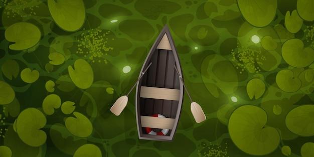 La barca di legno galleggia attraverso la palude con foglie di ninfea