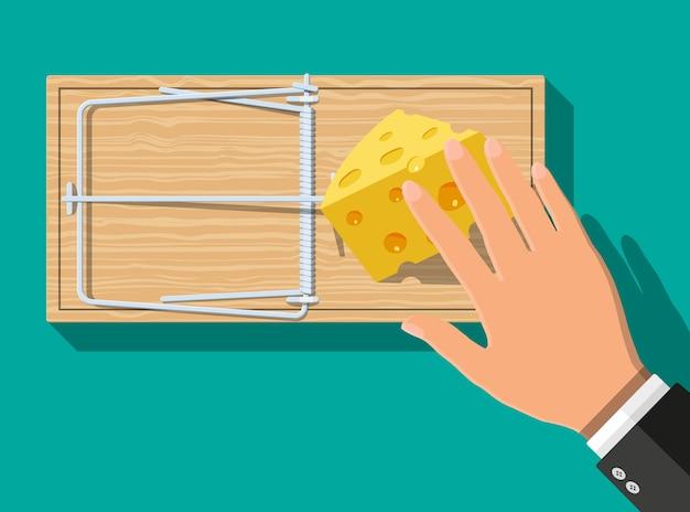 Trappola per topi in legno con formaggio e mano