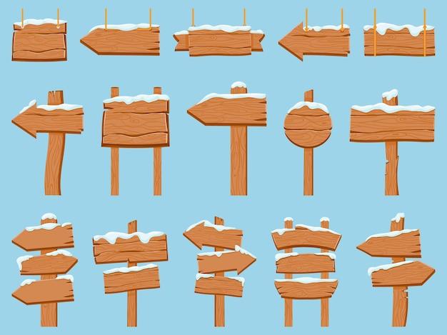 Insegne in legno con neve. striscioni in legno, pannelli sospesi e freccia di direzione. tavole del cartello invernale del fumetto con l'insieme di vettore dei cappucci innevati del ghiaccio. bordo invernale vintage, illustrazione innevata del segnale stradale