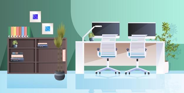 Posto di lavoro con monitor di computer interni moderni armadi vuoto senza persone stanza ufficio con mobili