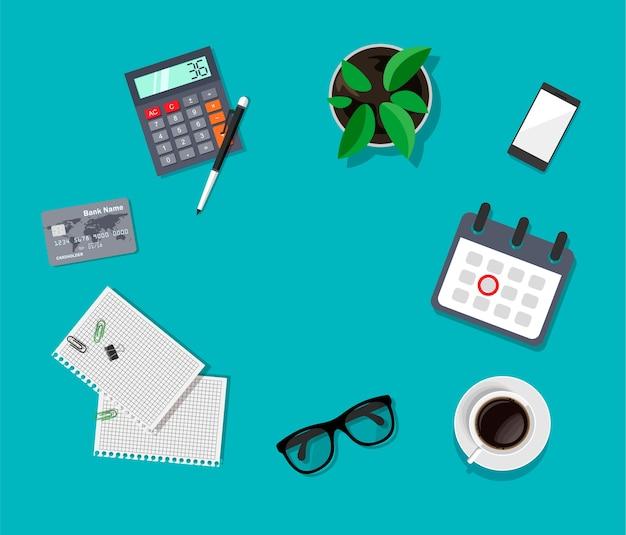 Vista dall'alto dell'area di lavoro scrivania da lavoro. occhiali, smartphone, caffè, calcolatrice, calendario, fogli di carta.