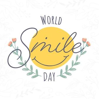 Testo della giornata mondiale del sorriso con faccina sorridente creativa su sfondo di foglie bianche.