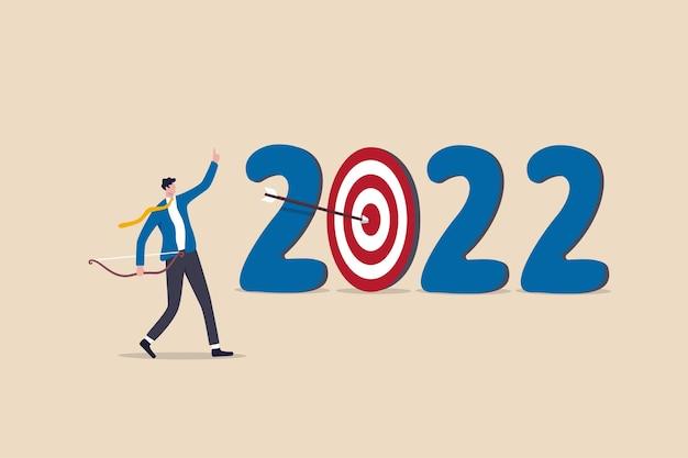 Obiettivo aziendale per l'anno 2022 o obiettivo di sviluppo personale, risoluzioni per il nuovo anno, piano di successo o concetto di realizzazione di carriera, uomo d'affari ambizioso sparare freccia al bersaglio bersaglio del numero dell'anno 2022.