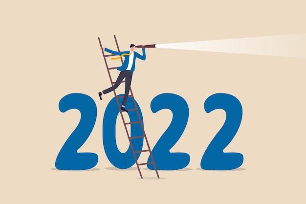 Prospettive economiche per l'anno 2022, previsioni o visionarie per vedere il futuro avanti, concetto di sfida e opportunità di business, uomo d'affari intelligente salire la scala per vedere attraverso il telescopio sul numero dell'anno 2022.