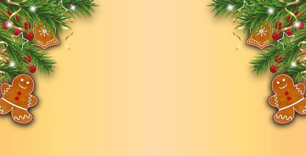 Sfondo giallo dorato di natale decorato rami di albero di natale con biscotti di panpepato, bacche di agrifoglio e nastri dorati.