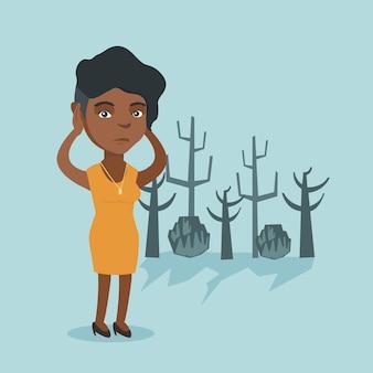 Giovane donna africana che sta in una foresta morta.