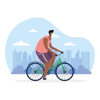 Giovane uomo afro in bicicletta equitazione indossando maschera medica