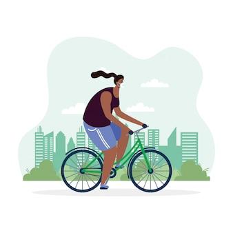 Bicicletta di guida della giovane donna afro che indossa maschera medica