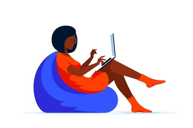 Giovane donna di colore che si siede nella borsa della sedia e lavora al computer. lavoro a distanza, home office, concetto di autoisolamento. illustrazione di stile piatto.