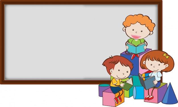 Bambini piccoli che leggono davanti a una lavagna in bianco