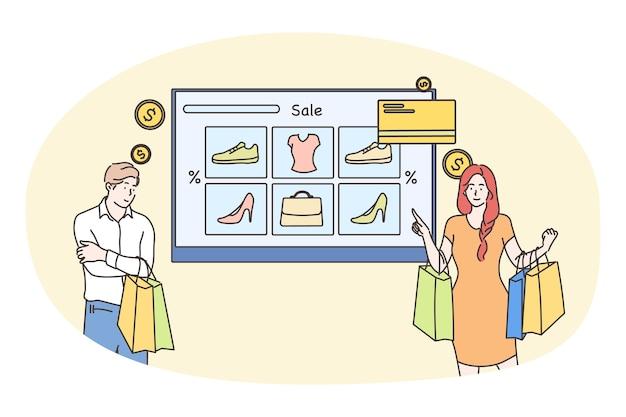 Coppia giovane uomo e donna clienti acquirenti che scelgono i vestiti dell'indumento che effettuano il pagamento online
