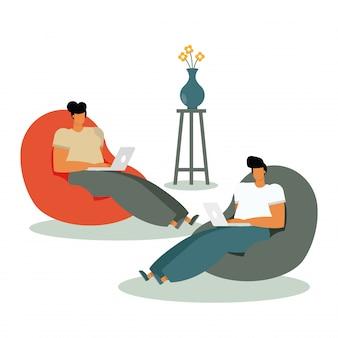 Giovani coppie che utilizzano i computer portatili e che lavorano nel salone