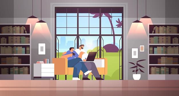 Coppia giovane con carta di credito utilizzando laptop shopping online concetto uomo donna ordinare merci insieme moderno soggiorno interno orizzontale full length