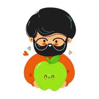 Il giovane uomo carino e divertente tiene in mano la mela verde