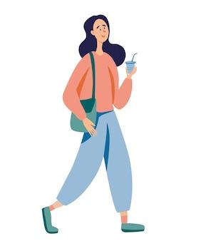 La giovane ragazza carina è in piedi e beve caffè la donna tiene in mano una tazza di caffè