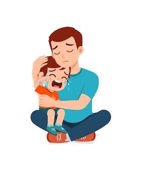Il giovane padre abbraccia un ragazzino piangente e cerca di consolarlo