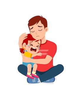 Il giovane padre abbraccia la bambina piangente e cerca di confortarla