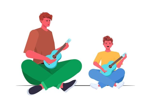 Giovane padre che insegna al figlio piccolo a suonare la chitarra concetto di paternità genitoriale papà trascorrere del tempo con il suo bambino a figura intera orizzontale