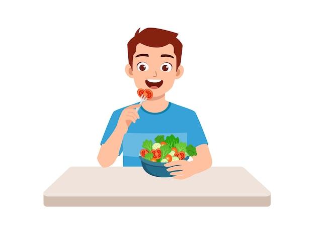 Il giovane uomo di bell'aspetto mangia frutta e verdura