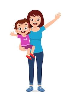 La giovane madre di bell'aspetto porta un bambino carino