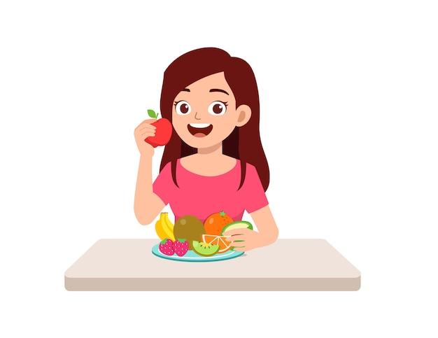 La giovane donna di bell'aspetto mangia frutta e verdura