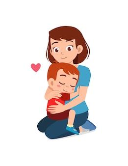 La giovane madre felice abbraccia il ragazzino carino