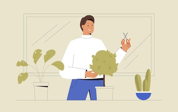 Giovane uomo sul balcone che coltiva fiori o piante d'appartamento verdi in una pentola