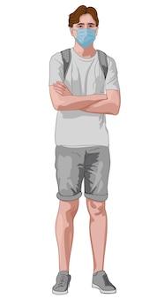 Giovane uomo in abiti grigi e maschera facciale blu in piedi con le mani incrociate