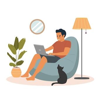 Il giovane si sta rilassando su una comoda poltrona a sacco e sta usando il computer portatile.