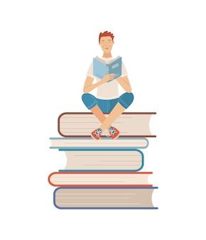 Giovane che legge un libro mentre è seduto su una pila di libri