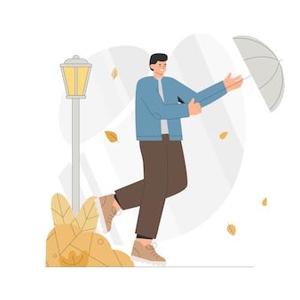 Il giovane corre con un ombrello in un ventoso autunno.