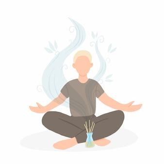 Giovane uomo seduto nella posa del loto con diffusore di aromi.