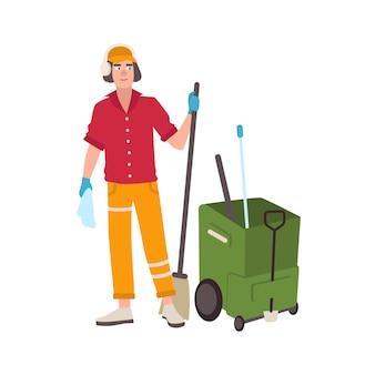 Giovane uomo che indossa le cuffie e uniforme in piedi accanto al carrello secchio mop e tenendo la scopa