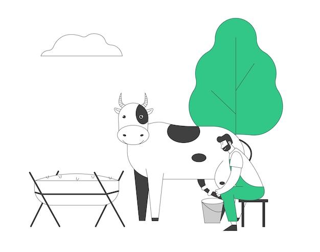 Giovane uomo lattaia in uniforme che si siede sulle feci che munge la mucca alla benna