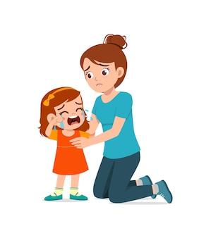 La giovane madre abbraccia la bambina piangente e cerca di confortarla