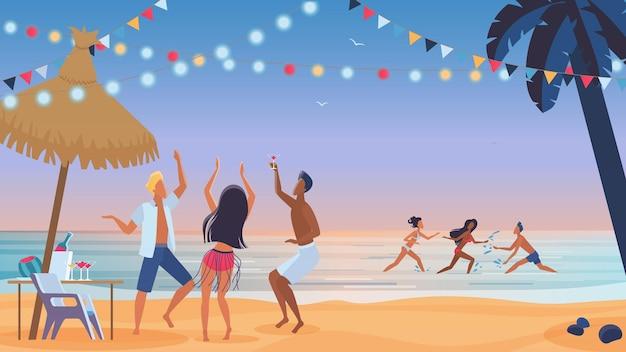 Amici di giovani che ballano sulla spiaggia al tramonto, festa in spiaggia serale, divertimento nell'acqua dell'oceano