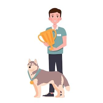 Giovane uomo sorridente e fiero cane huskies in piedi insieme alla medaglia d'oro e alla coppa dei campioni