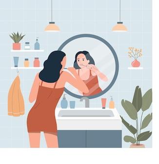 Giovane donna che si lava i denti davanti allo specchio del bagno. illustrazione di stile piano del fumetto di vettore