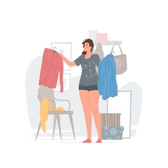 Giovane donna che sceglie i vestiti nella mattina a casa