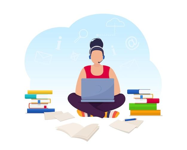 Giovane donna in cuffia seduta sul pavimento a casa e lavora al computer portatile libero professionista che lavora