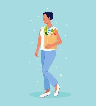 Sacchetto di carta della tenuta della giovane donna con i prodotti della drogheria. la ragazza porta gli acquisti in borse ecologiche. vendita di cibo