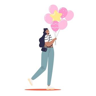 Giovane donna che tiene palloncini rosa